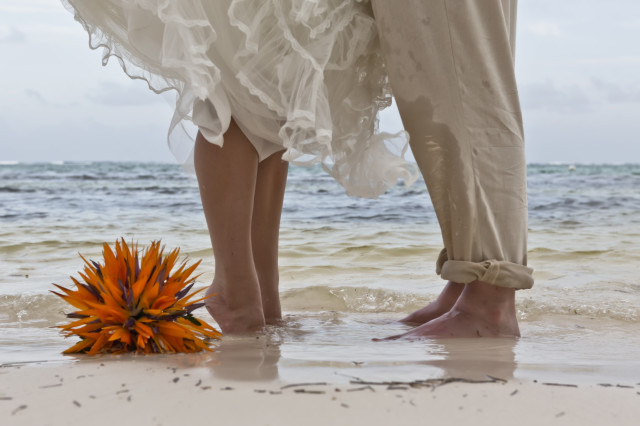 Bouquet hits the water on beach wedding in Belize with planner romantictravelbelize.com